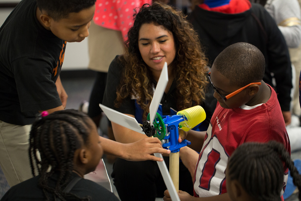 A Space Center Houston educator works with students participating in the Exploration Academy at the center.