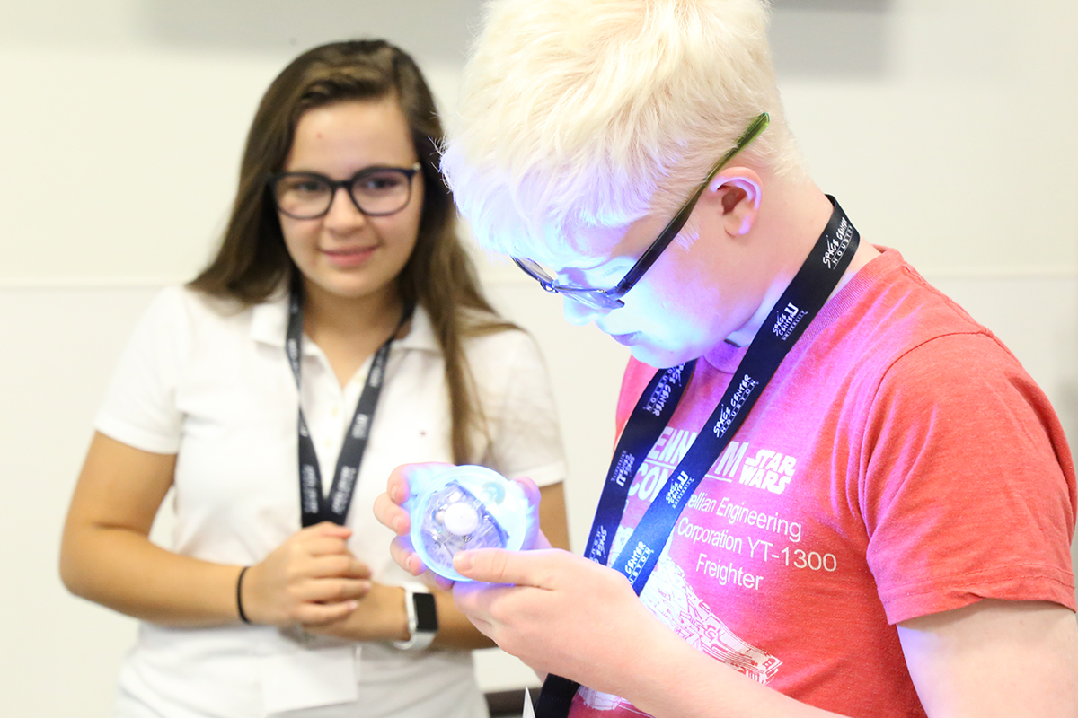Students with visual impairments examine robot in Space Center University